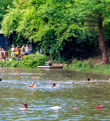 The fair is at Hampstead Heath, people are picniking and swimming
